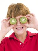 Young boy holding kiwi halves over eyes smiling - stock photo