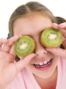 Young girl holding kiwi halves over eyes smiling - stock photo