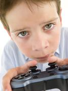 Young boy using videogame controller and concentrating Stock Photos