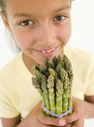 Young girl holding bunch of asparagus and smiling - stock photo
