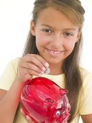 Young girl putting coin into piggy bank smiling Stock Photos