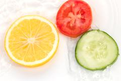 lemon cucumber and tomato in the water on a white background - stock photo