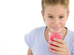 Young girl with glass of juice smiling - stock photo