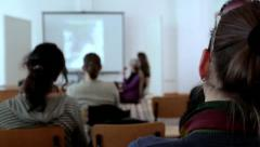 Students listening to a teacher in the classroom. Focus on a girl. Candid shot. Stock Footage