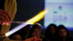 A glass blower is working with test-tube. Projection screen and students looking - stock footage