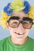 Young boy wearing clown wig and fake nose smiling Stock Photos