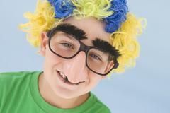 Young boy wearing clown wig and fake nose smiling - stock photo