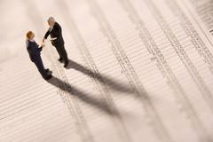 Figurines Of Two Businessmen Shaking Hands On A Financial Newspaper Stock Photos