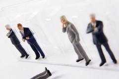 Row Of Businessman Figurines, With One Fallen Out Of Line Stock Photos