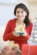 Woman Excited To Open Christmas Present Stock Photos
