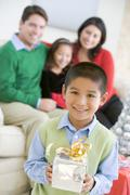 Young Boy Standing Holding Christmas Present,With His Parents And Sister In The - stock photo