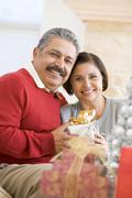 Middle Aged Couple Sitting On Sofa Holding Christmas Present Stock Photos