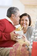 Middle Aged Couple Affectionately Sitting And Holding Christmas Present Stock Photos