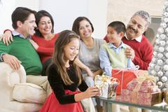 Family Sitting On Sofa In Front Of Christmas Presents,Young Girl Selecting A Stock Photos