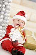 Baby In Santa Costume At Christmas Stock Photos