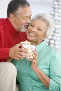 Senior Couple Exchanging A Christmas Gift Stock Photos