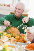 Man Carving Up Turkey At Christmas Dinner Stock Photos