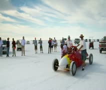 Men push streamlined racecar on Bonneville salt Flats Stock Footage
