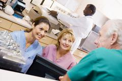 Nurses Talking At The Reception Area In A Hospital - stock photo