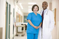 Doctor And Nurse Standing In A Hospital Corridor Stock Photos