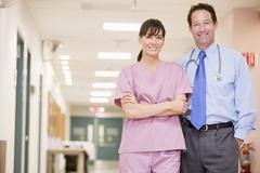 Doctor And Nurse Standing In A Hospital Corridor Stock Photos