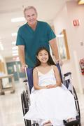 An Orderly Pushing A Little Girl In A Wheelchair Down A Hospital Corridor - stock photo