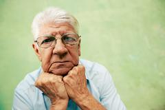portrait of serious old man looking at camera with hands on chin - stock photo