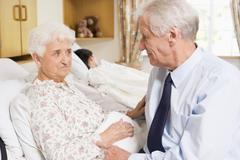 Senior Man Sitting With His Wife In Hospital Stock Photos
