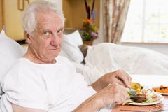 Senior Man Eating Hospital Food In Bed Stock Photos