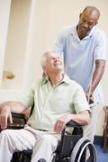 Nurse Pushing Man In Wheelchair - stock photo