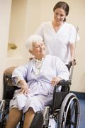 Nurse Pushing Woman In Wheelchair - stock photo