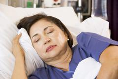 Senior Woman Asleep In Hospital Bed - stock photo