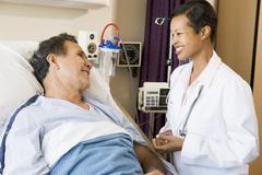 Doctor And Patient Talking To Each Other,Smiling Stock Photos