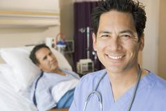 Doctor Smiling In Patients Room Stock Photos