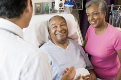 Senior Couple Talking,Smiling With Doctor Stock Photos