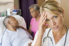 Doctor With Headache In Patients Room - stock photo