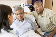 Doctor Talking To Senior Couple - stock photo
