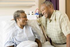 Senior Couple Smiling At Each Other In Hospital - stock photo