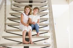 Two Young Girls Sitting On A Staircase At Home - stock photo