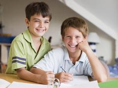 Two Young Boys Doing Their Homework Together - stock photo