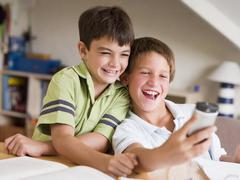 Two Young Boys Distracted From Their Homework, Playing With A Cellphone - stock photo