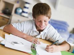 Young Boy Doing His Homework While Listening To Music On His MP3 Player Stock Photos