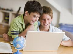 Two Young Boys Using A Laptop At Home - stock photo