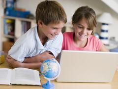 Boy And Girl Doing Their Homework On A Laptop Stock Photos