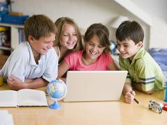 Group Of Young Children Doing Their Homework On A Laptop - stock photo
