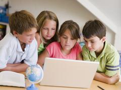 Group Of Young Children Doing Their Homework On A Laptop Stock Photos