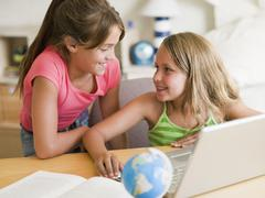 Two Young Girls Doing Homework On A Laptop - stock photo