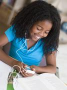 Young Girl Distracted From Her Homework, Playing With An MP3 Player Stock Photos