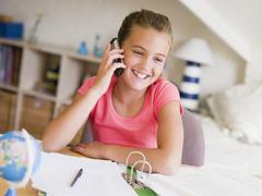 Young Girl Distracted From Her Homework, Talking On A Cellphone - stock photo