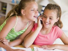 Young Girls Distracted From Their Homework, Talking On A Cellphone - stock photo